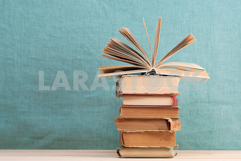 Stack of hardback books on blue cloth. Back to school. Copy space — Image 45339