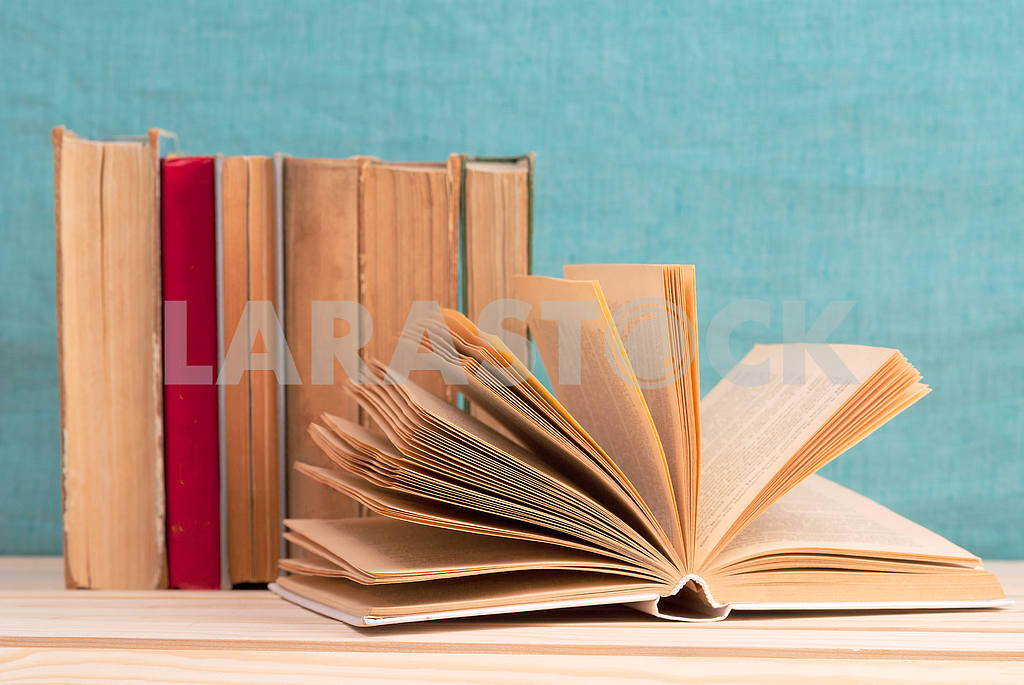 Stack of hardback books on blue cloth. Back to school. Copy space — Image 45342