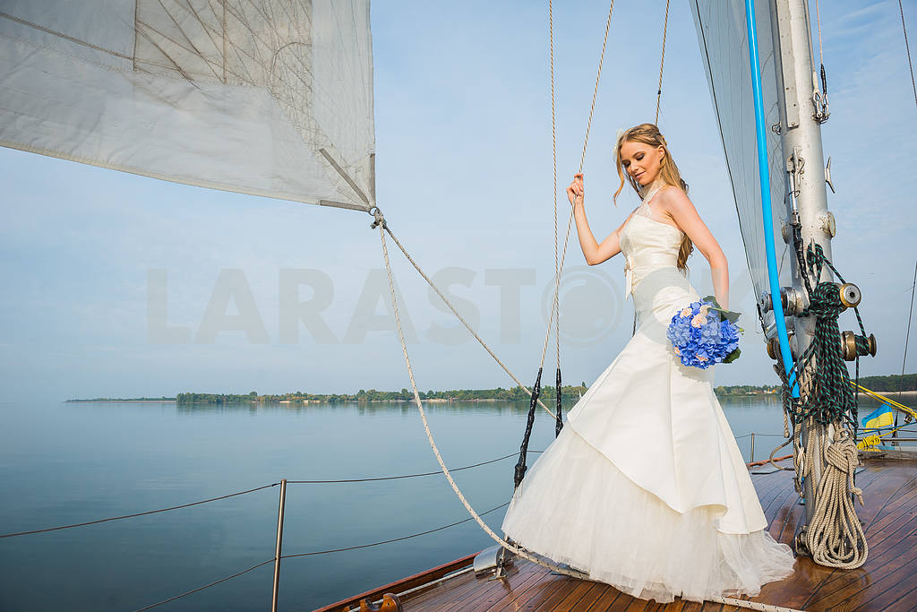 Beautiful blonde bride in a long white dress poses on a sailing yacht at sea with the blue bouquet in her hand and the other hand on the rope on a sunny day — Image 46062