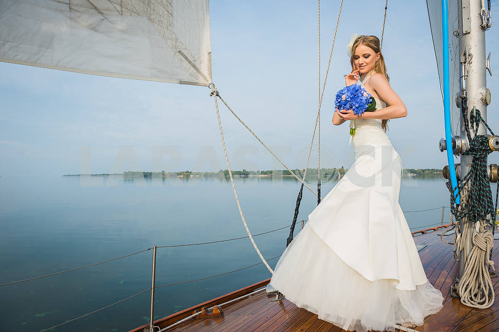 Beautiful blonde bride in a long white dress poses on a sailing yacht at sea with the blue bouquet in her hands on a sunny day — Image 46063