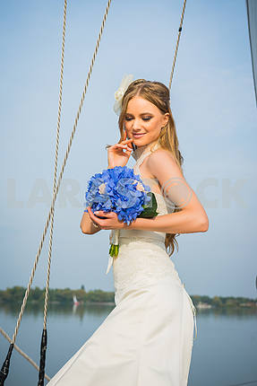 Beautiful blonde bride in a long white dress poses on a sailing yacht at sea with the blue bouquet in her hands on a sunny day