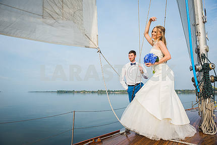 Honeymoon sailing - Stylish young bride and groom standing on board the sailing yacht