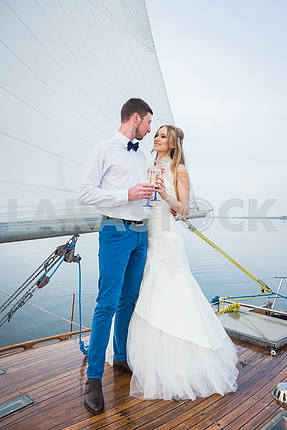 Happy bride and groom hugging on a yacht - looking into each other