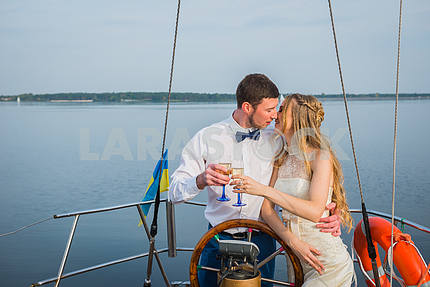 Happy bride and groom hugging on a yacht - kissing each other. Happy bride and groom hugging on a sailing yacht with the champagne  in their hands on a sunny day; stylish, long dress, bow tie