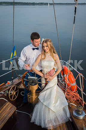Happy bride and groom hugging on a sailing yacht with the champagne  in their hands on a sunny day; stylish, long dress, bow tie
