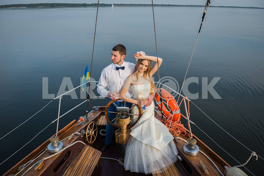 Newly married couple stand on white yacht, outdoor. The steering wheel of the yacht.  wedding on the sailing yacht — Image 46074