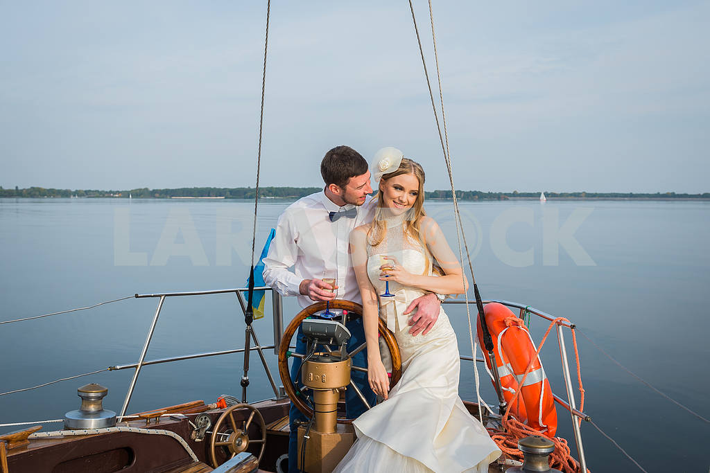 Happy bride and groom hugging on a sailing yacht with the champagne  in their hands on a sunny day; stylish, long dress, bow tie. The steering wheel of the yacht. — Image 46075