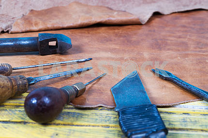 Leather craft tools on a wooden background. Leather craftmans work desk . Piece of hide and working handmade tools on a work table