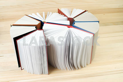 Open book, stack of hardback books on wooden table. Back to school. Copy space