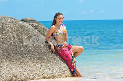 Красивая молодая девушка с коктейлем в руке на пляже