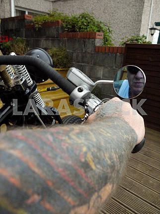 Tattooed Arm Holdng Handlebars.
