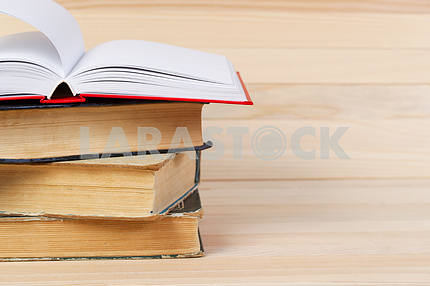 Stack of hardback books on wooden table. Back to school.