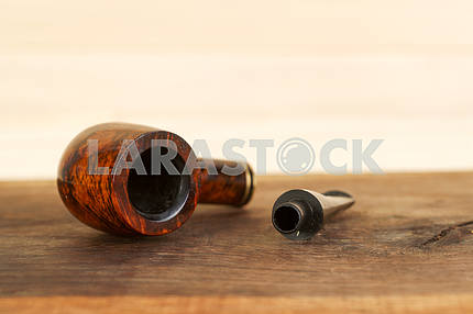 Smoking pipe on a wooden table. Aroma. Copy space