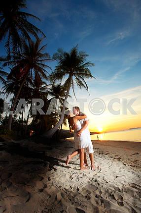 Молодая пара, обниматься на пляже на закате