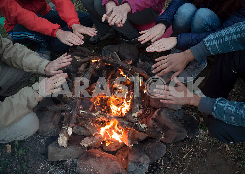 Young men and women hands warm by the fire. They sit around the — Image 47726