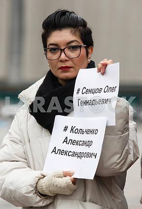 Тамила Ташева держит листы с именами политзаключенных