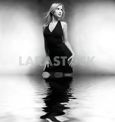 Beautiful young woman in a black dress stands in the water