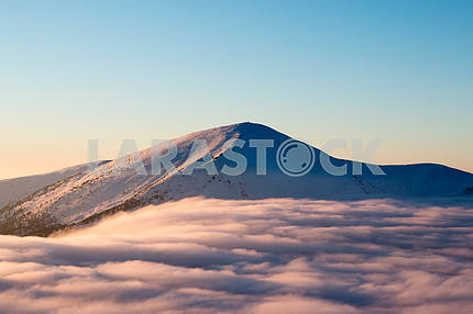 Snow-capped mountains rising above a fluffy cloud, cold, frosty