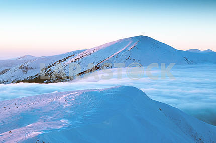 Snow-capped mountain peaks, among them a fluffy cloud, cold, fro