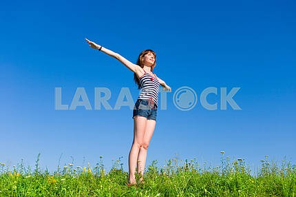 Happy young woman enjoying summer. Against the backdrop of blue