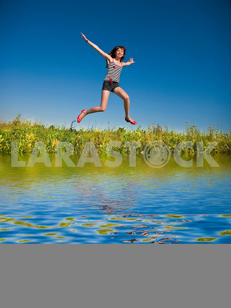 Happy young woman jumping in a field — Image 4824