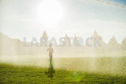 The boy runs on a green golf courses are watered.