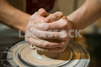 Potter makes a jug on a potter's wheel