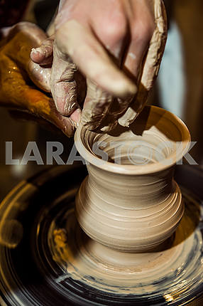 Potter makes a jug on a potter's wheel