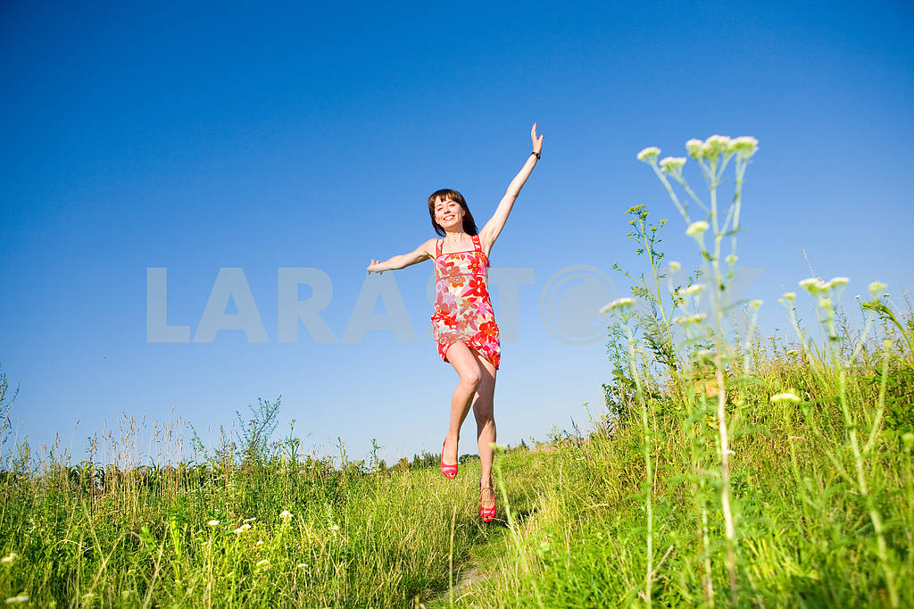 Happy girl fleeing on a meadow. In red dress and red shoes. Agai — Image 4874