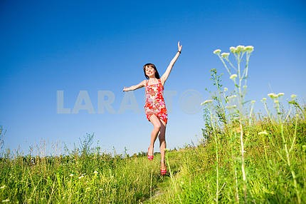 Happy girl fleeing on a meadow. In red dress and red shoes. Agai