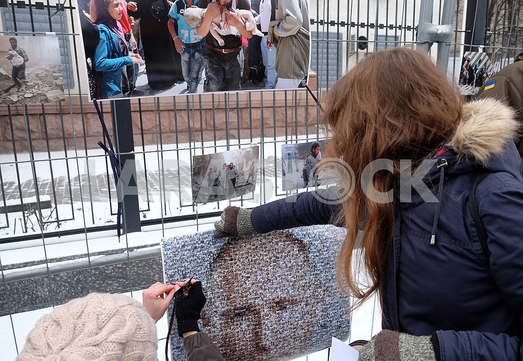 The girl attaches a portrait of Putin to the fence of the embassy — Image 49156