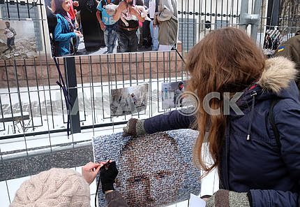 The girl attaches a portrait of Putin to the fence of the embassy