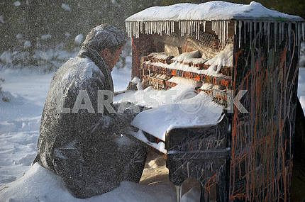 Musician sitting at a grand piano covered with snow.