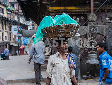 A man carries on his head a basket of goods