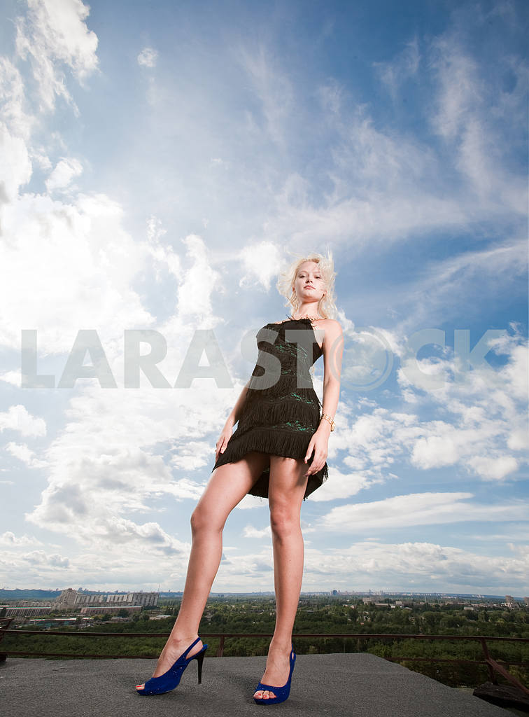 Beautiful girl stending against a cloudy sky — Image 4948