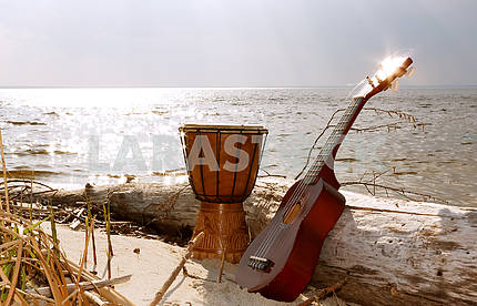 Ukulele and ethnic drum on a sunny beach.