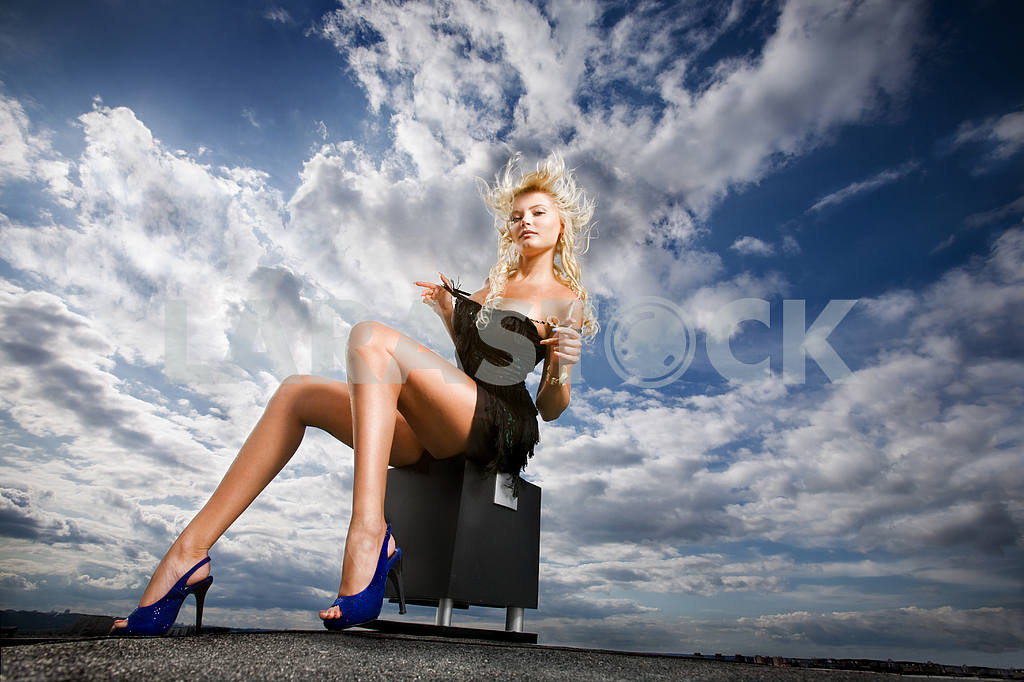 Beautiful girl sitting against a cloudy sky — Image 4949