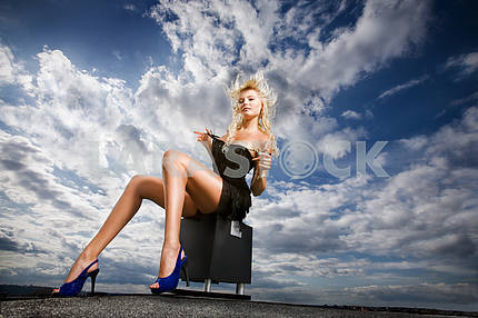 Beautiful girl sitting against a cloudy sky