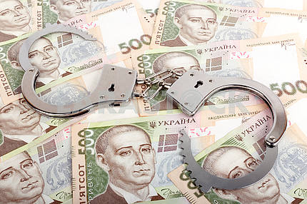 Ukrainian currency and handcuffs.