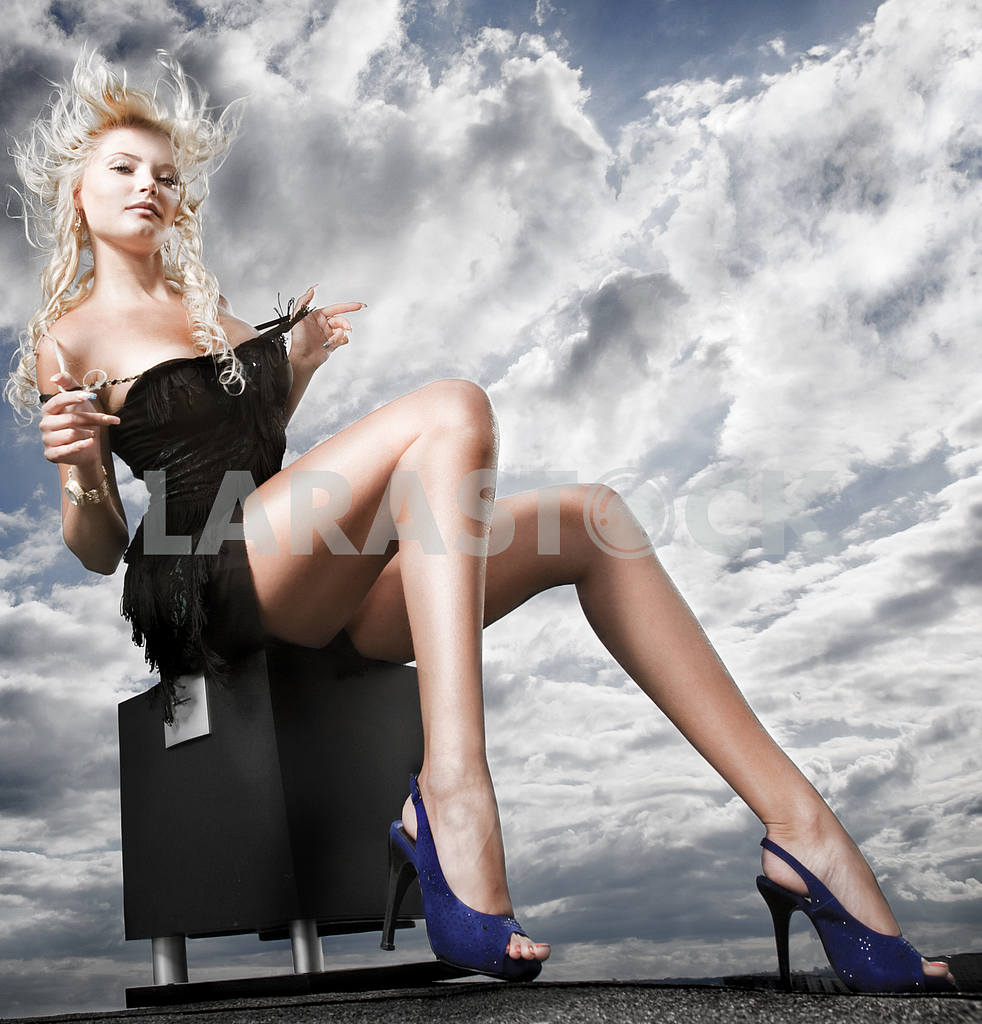 Beautiful girl sitting against a cloudy sky — Image 4950