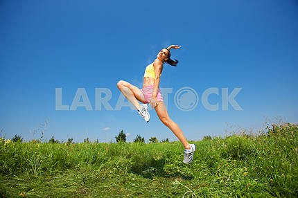 Young athletic woman jumping on grass