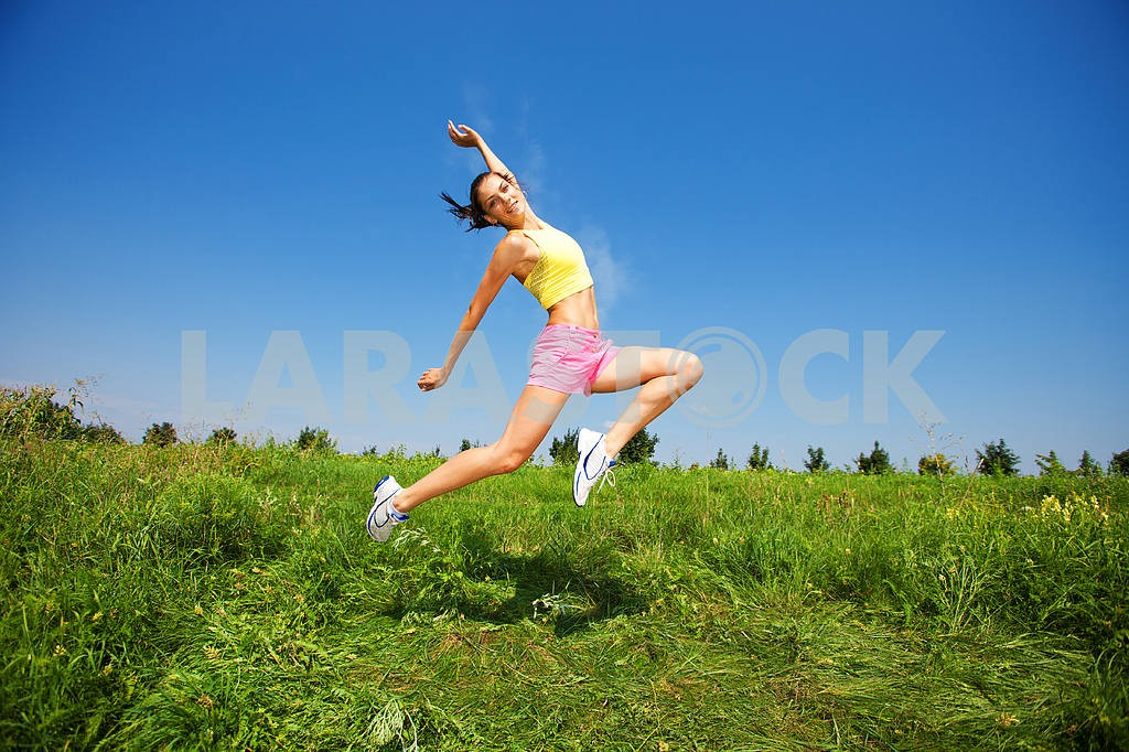 Young athletic girl jumping on grass — Image 4974