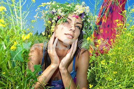 Happy young beautiful girl lying in flowers