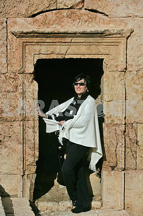 A woman in a window opening on the ruins of the ancient city of Jarash