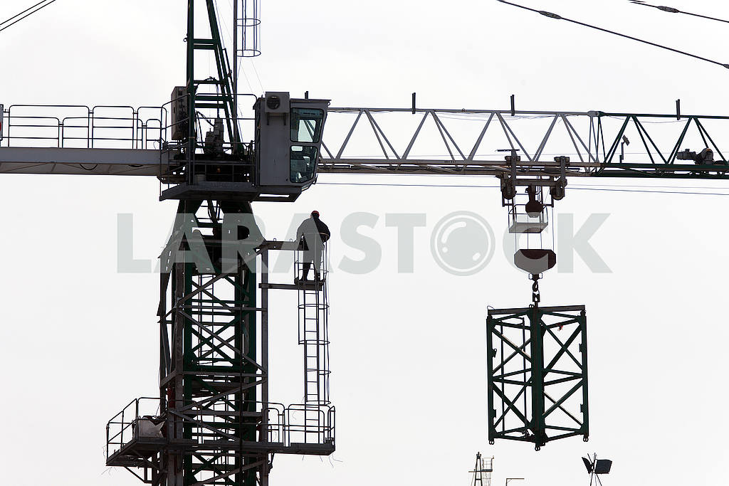 Silhouettes of cranes with a load on the construction of buildin — Image 49977