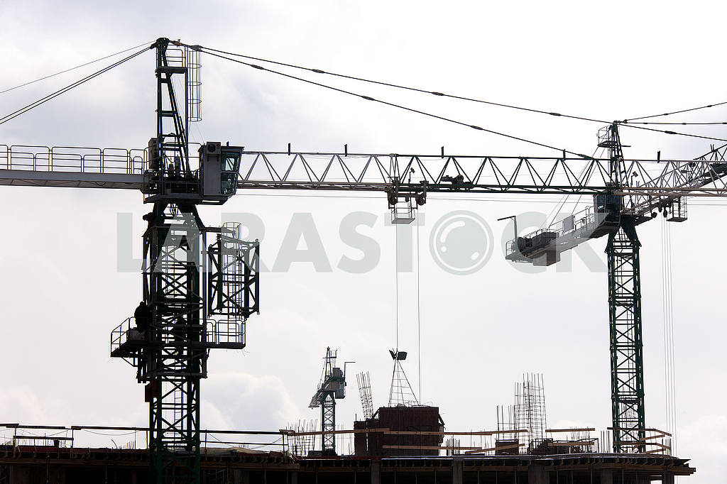 Silhouettes of cranes with a load on the construction of buildin — Image 49980