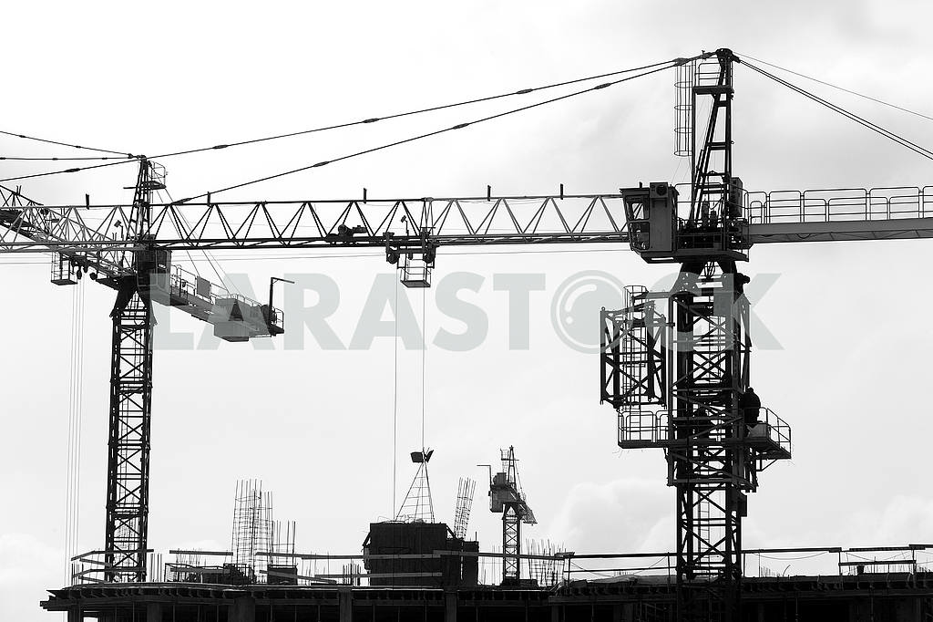 Silhouettes of cranes with a load on the construction of buildin — Image 49981