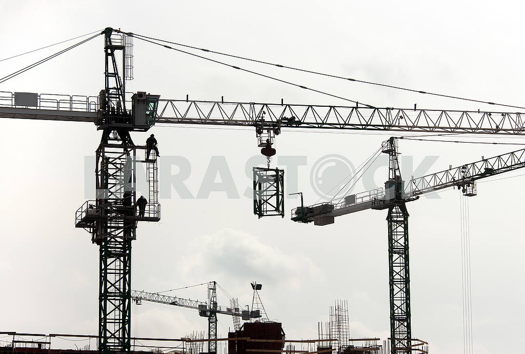 Silhouettes of cranes with a load on the construction of buildin — Image 49982