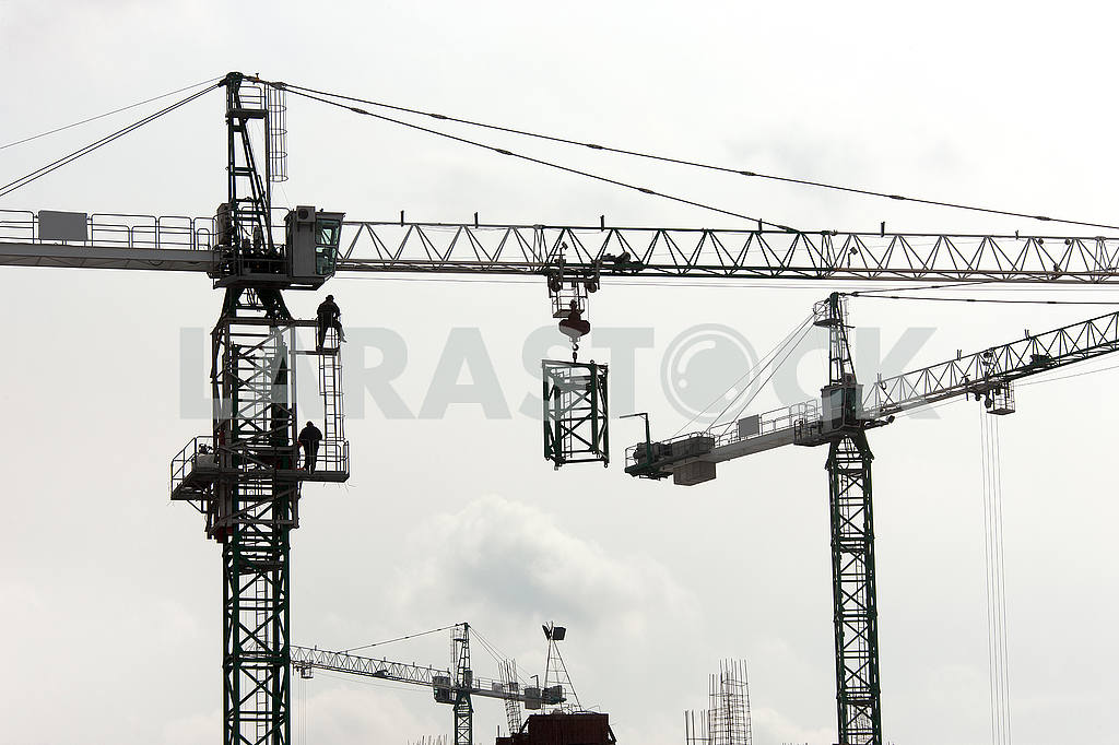 Silhouettes of cranes with a load on the construction of buildin — Image 49984