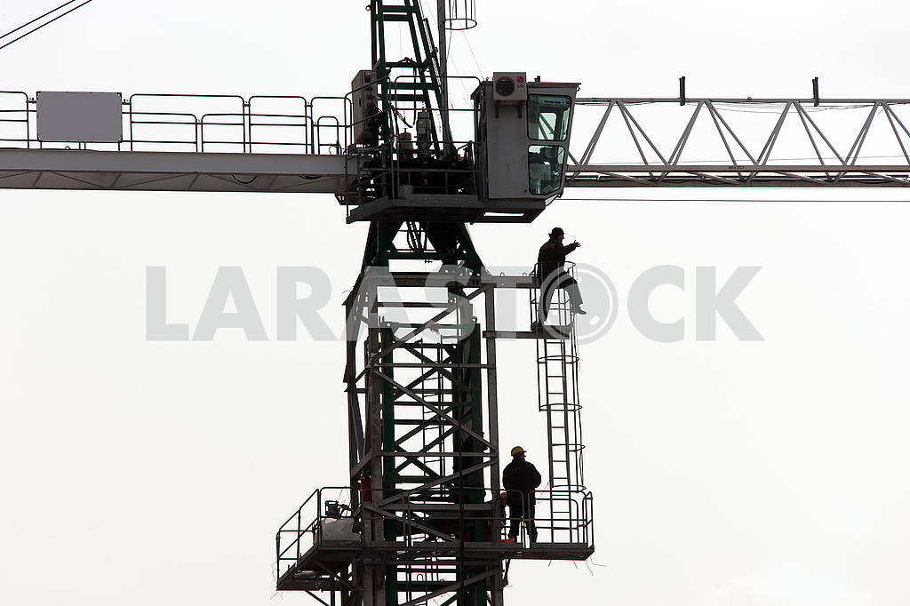 Silhouettes of cranes with a load on the construction of buildin — Image 49985